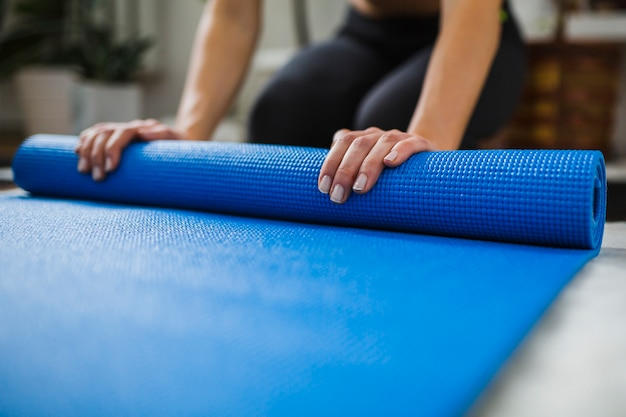 Crop woman rolling up stretching mat