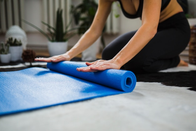 Crop woman rolling up yoga mat