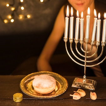 Crop woman sitting near hanukkah symbols