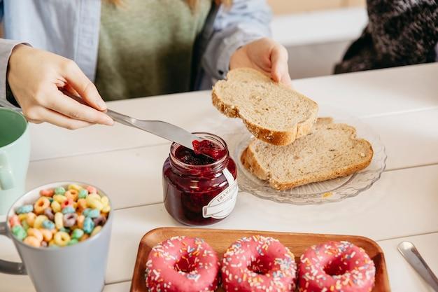 作物の女性はパンにジャムを塗りつぶす