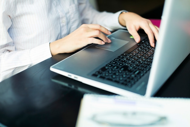 Raccolga la donna che per mezzo del computer portatile alla tavola