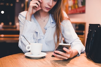 Crop woman using smartphone at cafe table