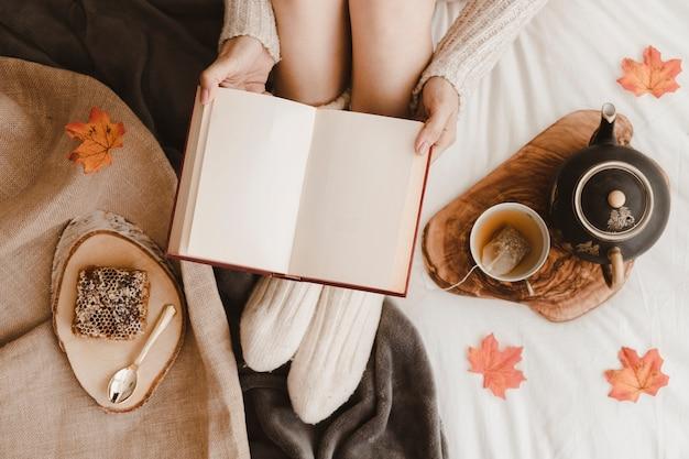 Raccolga la donna con il libro vicino a tè ed a nido d'ape