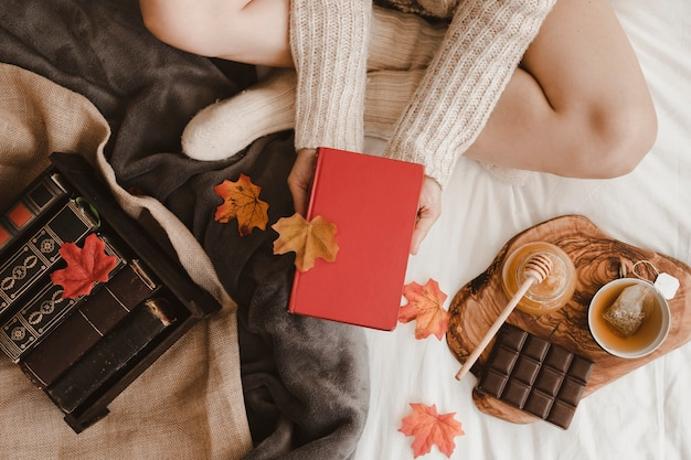 Raccolga la donna con il libro vicino a tè e foglie