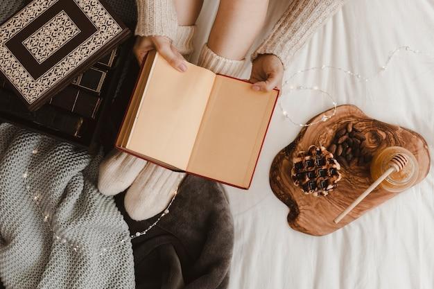 ワッフルとハニーの近くの本で作物の女性