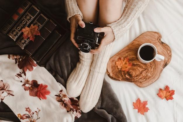 Ritaglia la donna con la macchina fotografica vicino a libri e tè