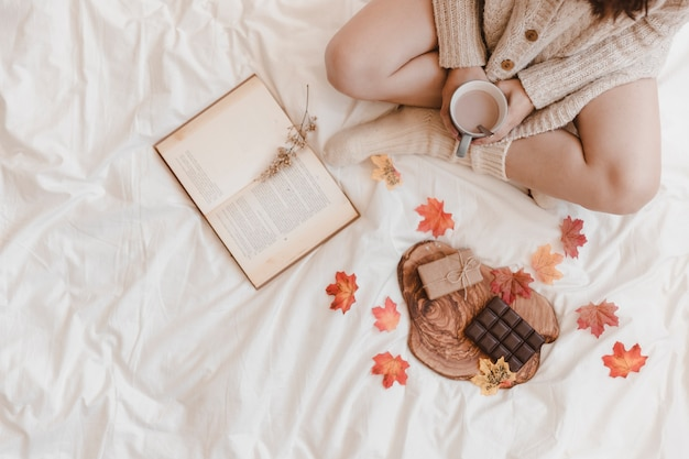 Crop woman with coffee and book near chocolate and gift
