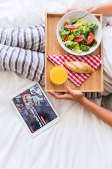 Crop woman with healthy food near tablet with netflix site