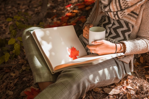 Crop woman with mug reading in autumn forest