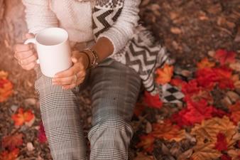 Crop woman with mug sitting on ground