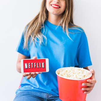 Crop woman with popcorn and smartphone with netflix logo