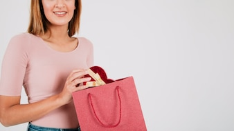 Crop woman with present in bag