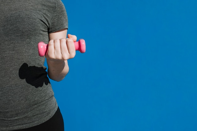 Crop woman with small dumbbell