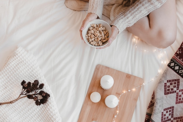 Crop woman with snack on bed