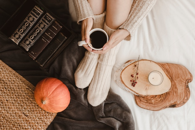 Crop woman with tea near pumpkin and books