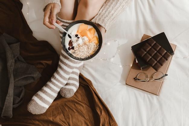 Crop woman woman breakfasting near books and chocolate
