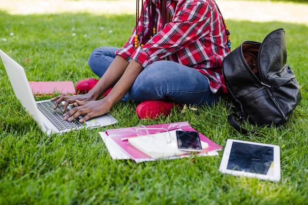 公園でラップトップを使って作業する作物女性