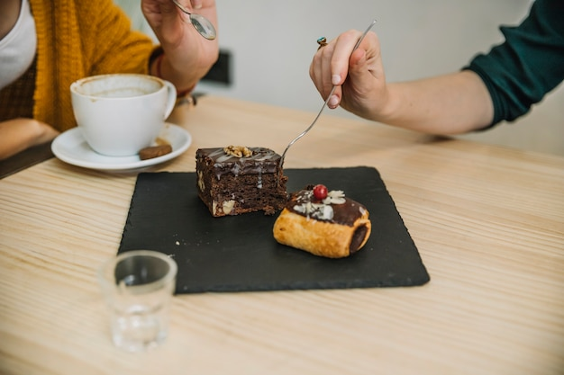 Raccolga le donne che mangiano il dessert in caffè