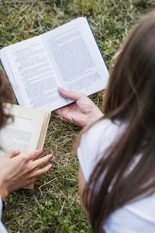 Raccolga gli amici delle donne che leggono i libri su erba
