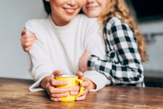 Crop women hugging while sitting at table
