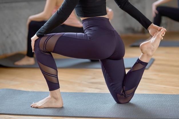 Crop of women practicing yoga in hall.