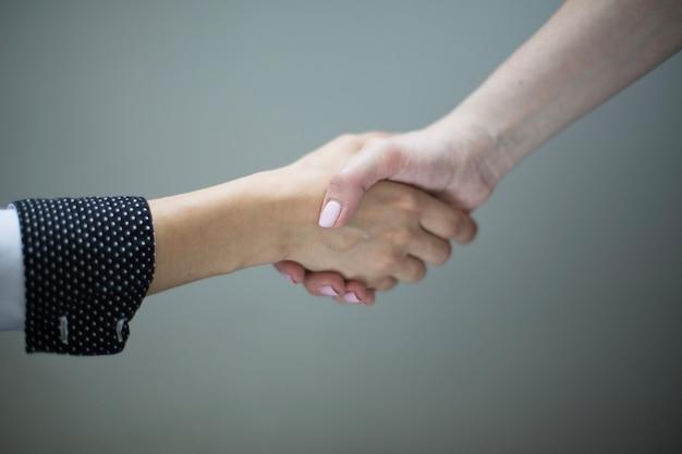 Crop women shaking hands