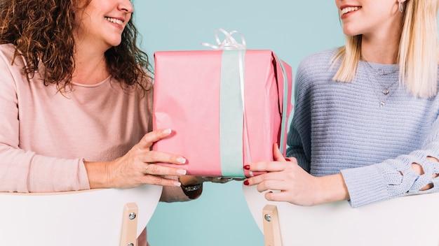 Обрезать женщин с подарочной коробкой на стульях