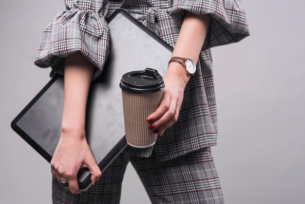 Crop женщина, держащая ноутбук и чашка