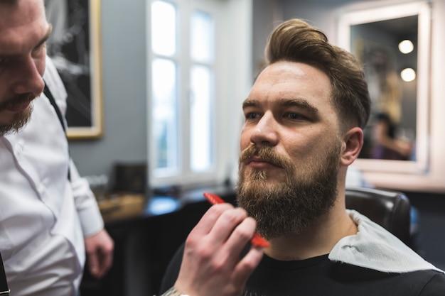Crop стилист, расчесывающий бороду клиента