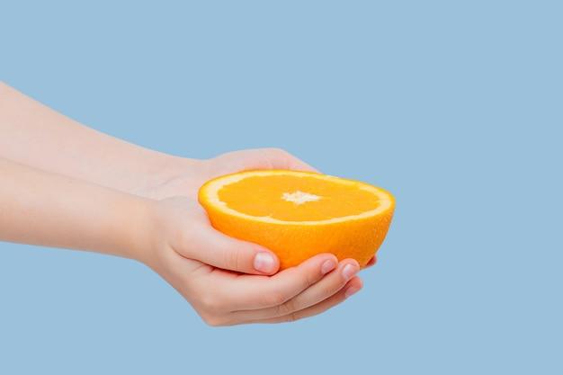 파란색에 고립 된 소녀의 손에 자른 반 오렌지