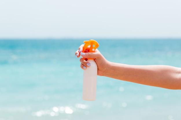 해변에서 자외선 차단제 스프레이를 들고 여자의 손의 자른 이미지.
