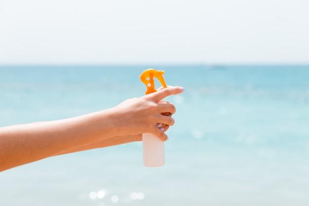 바다 배경에서 썬 스크린 스프레이를 들고 여자의 손의 자른 이미지.