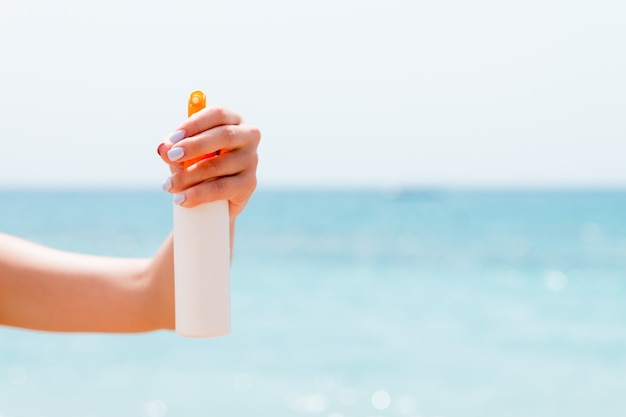 Croped image of woman's hand holding sunblock spray at the beach.