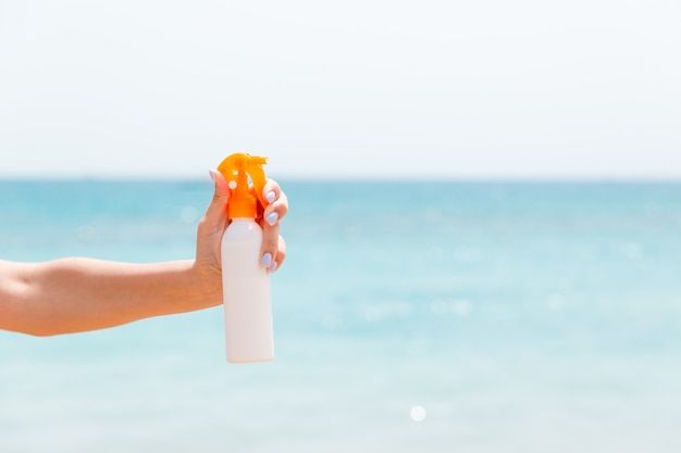 Croped image of woman's hand holding sunscreen spray at the sea background.