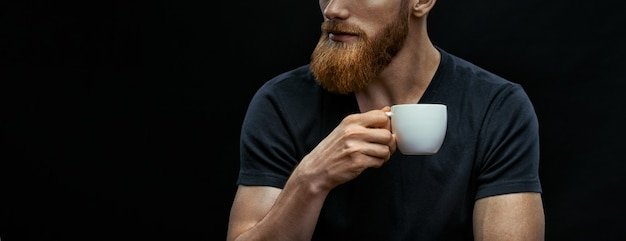 Croped shot of bearded man drinking coffee. resting man drinking espresso coffee holding cup of coffee in hand. studio shot on black background wit copy space on left