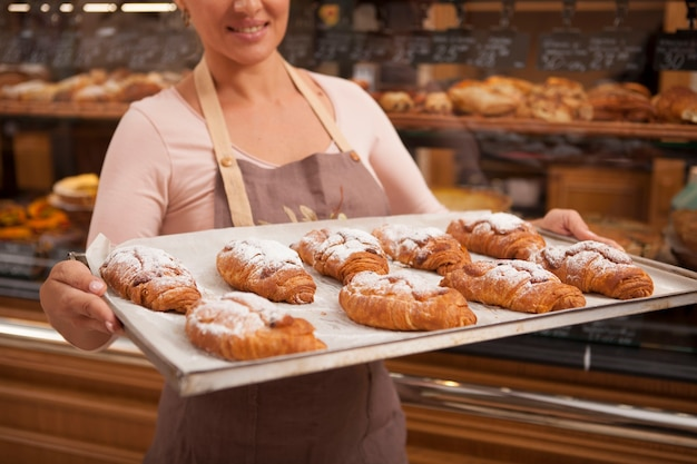 Croped shot of a tray full of delicious sweet croissants in the hands of female baker