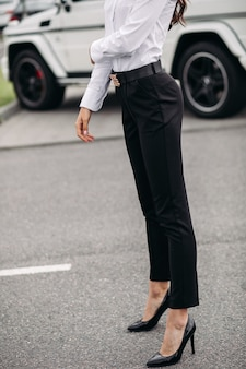 Croppe photo of fashionable and stylish lady dressed in black pants and white blouse posing on the background of a car outdoors
