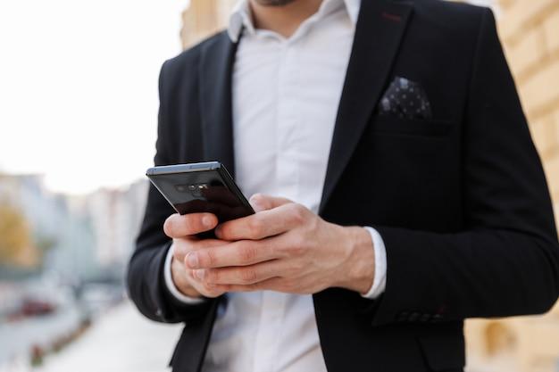 Обрезанный молодой бизнесмен в костюме, стоящий в городе, с помощью мобильного телефона