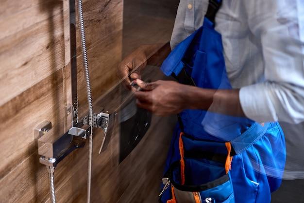 シャワー室の固定蛇口を修理するトリミングされたアフロアメリカン配管工の男、側面図の肖像画、シャワーを修理する青いオーバーオールのプロの熟練した便利屋。サービス、組み立てコンセプト。閉じる