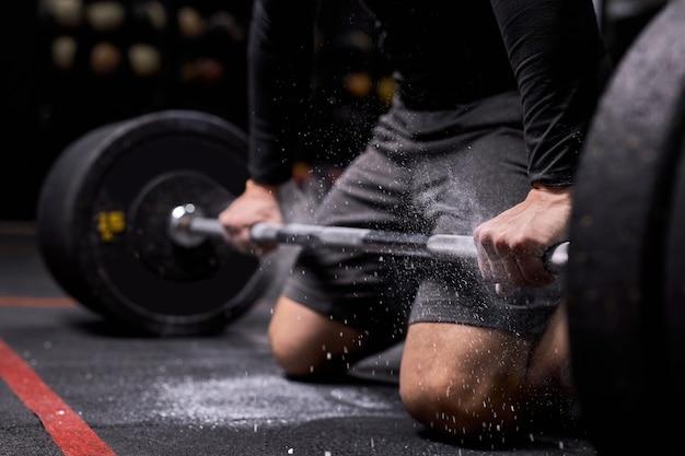 クロップドアスリートの男性がクロスフィットトレーニングの準備をしています。自信のあるパワーリフターは、タルクを使用して重い体重を上げる準備をしています。モダンなジム、フィットネスセンター