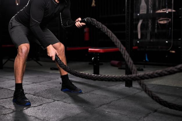 ジムでロープを使ってクロスフィットエクササイズをし、トレーニング、トレーニングに集中して集中しているクロップドアスリートマン。人とスポーツ、クロスフィットコンセプト