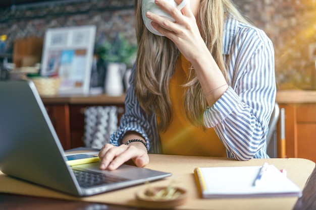 Обрезанная красивая дама девушка работает за ноутбуком на кухне и пьет кофе дома, используя