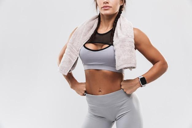 아름 다운 젊은 놀라운 강한 스포츠 피트 니스 여자는 수건을 들고 흰 벽 배경 위에 고립 된 포즈를 잘립니다.