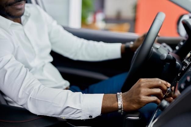 Обрезанный черный мужчина осматривает новый автомобиль изнутри