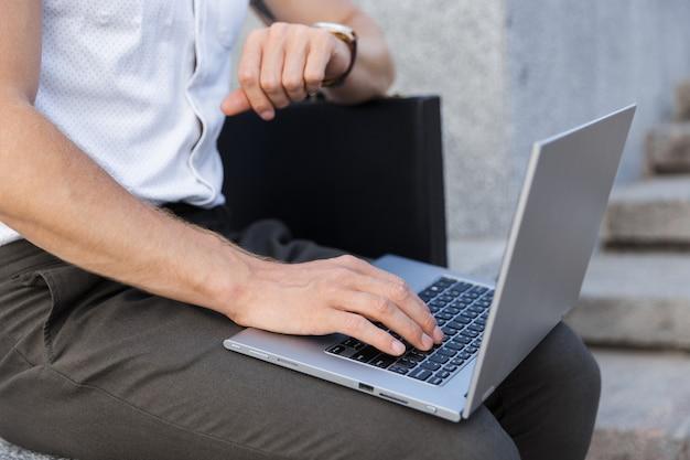 Обрезанный деловой человек с портфелем, используя портативный компьютер и наручные часы, сидя у лестницы