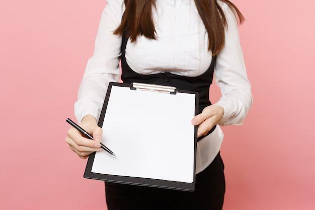 정장을 입은 자른 비즈니스 여성은 분홍색 배경에 격리된 빈 시트 작업 공간 복사 공간이 있는 클립보드 태블릿에 서명을 위해 펜을 제공합니다. 여사장님. 성취 경력 부입니다. 광고.