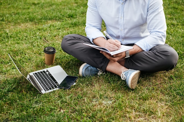 Cropped caucasian man in business clothing, sitting on grass in park with legs crossed and writing down notes in notebook while working on laptop