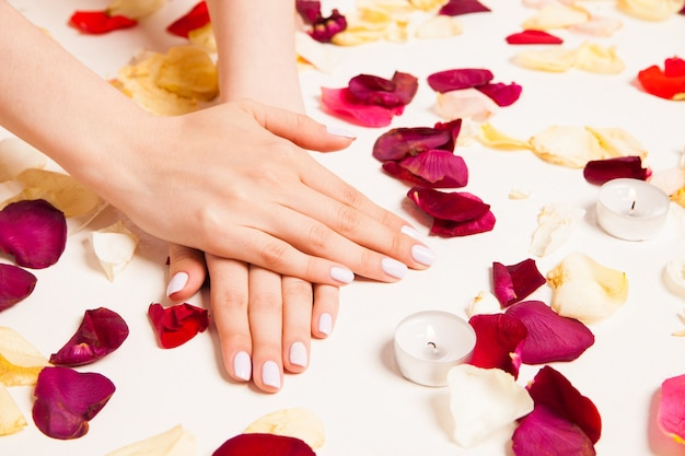Cropped close up female gentle hands laying crossed on white surface surrounded with rose petals and candles.