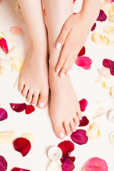 Cropped close up female tender hand laying on feet on white surface with rose petals and candles.