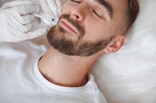 주름 부위에 얼굴 필러 주사를 받고 수염 난 남자의 자른 가까이